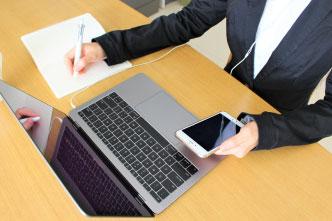 スマホとペンを持ち、パソコンを開いて仕事する様子