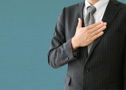 胸に手を添えるスーツの男性